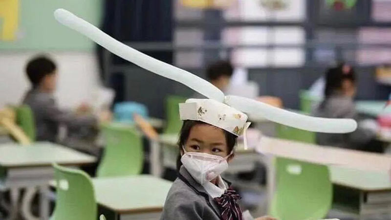 kids in china wearing social distancing hats